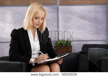Attractive businesswoman sitting in elegant office armchair, busy taking notes into personal calendar.