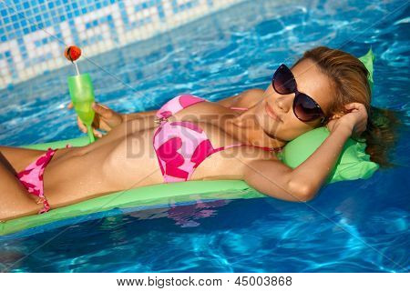Sexy girl in bikini relaxing on water at summertime, laying on airbed in pool.