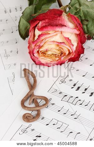 Treble clef and rose on musical background