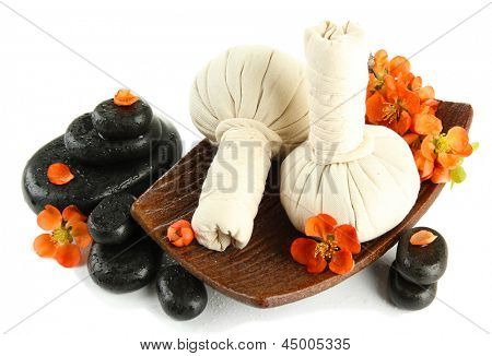 Herbal compress balls for spa treatment and spa stones isolated on white