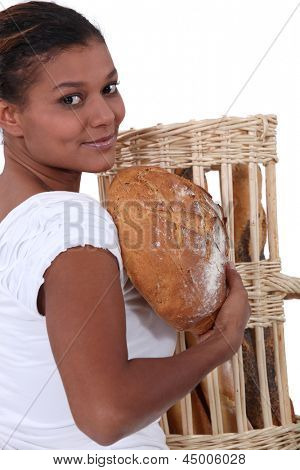 young black woman holding bread in her arms