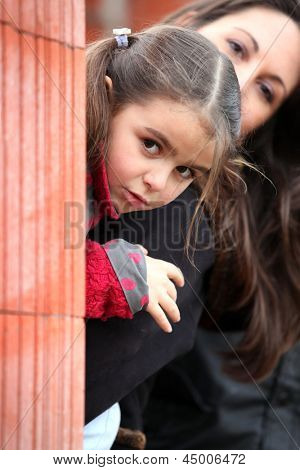 Mother and daughter peering from behind brick wall