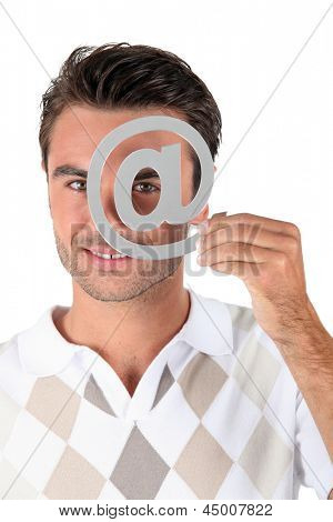Man holding metallic at symbol over eye