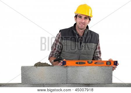 Stonemason using a bubble level