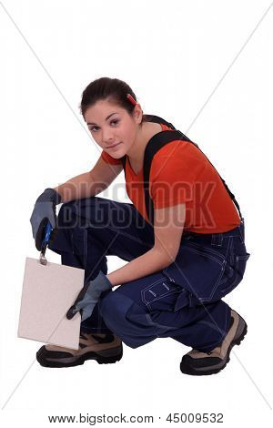 handywoman holding a tile