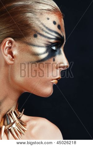 Profile portrait of young beautiful woman with face-art