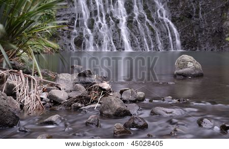 Stream running over rocks with waterfall in the background