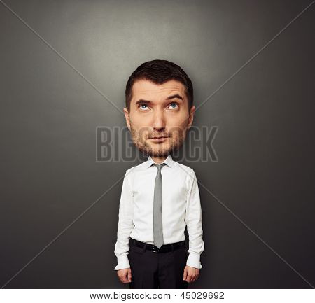 funny picture of bighead man in white shirt and tie over dark background