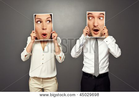 man and woman holding surprised faces. concept photo over grey background