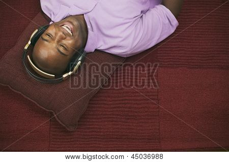 Young man lying on floor and listening to music