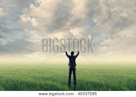 Asian businessman stand on grassland and open arms feel free or success against sunny light under dramatic cloudy sky. Photo compilation concept about business, success, win, challenge or dream.