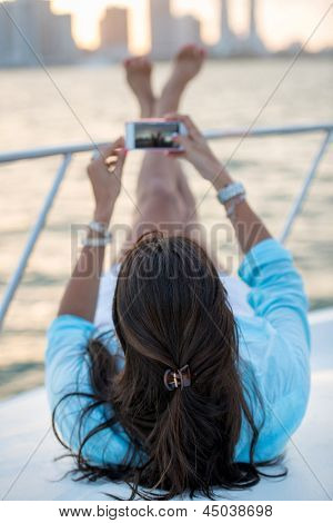 Woman relaxing taking picture on a yacht with cell phone