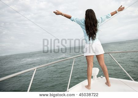 Woman enjoying sailing on a boat with arms open