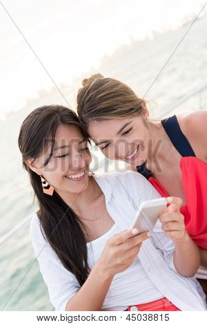 Happy women using an app on a cell phone on a yacht