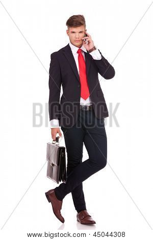 full length picture of a young business man standing with his legs crossed and holding a briefcase while speaking at the phone and looking at the camera with a serious look on his face