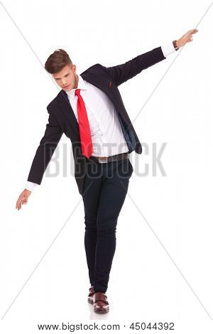full length picture of a young business man balancing on an imaginary rope and looking down. isolated on white background