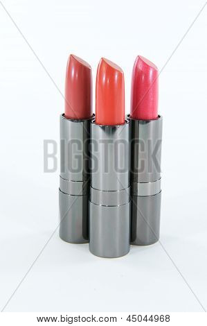 Cluster Of Three Lipstick Cases Standing Against A White Background