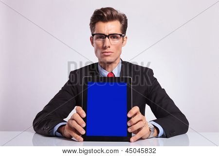 young business man sitting at the desk and showing you his tablet, on gray background