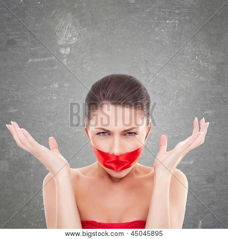 angry woman with mouth covered with a red ribbon
