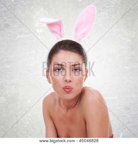 beautiful young woman wearing cute bunny ears looking and kissing the camera