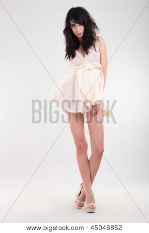 sexy young fashion woman posing with her legs crossed and one of her hands on her thigh. on gray background