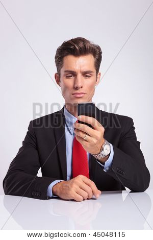 young business man sitting at the desk and writing a message on his phone