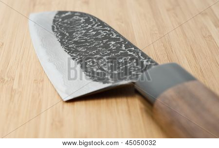 Japanese damascus carbon steel knife on wooden plank, close-up