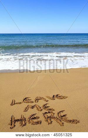 ?Leave me here? written on golden sandy beach