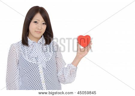 Young beautiful woman holding a heart