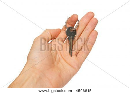 Silver Key In A Hand Isolated On White.