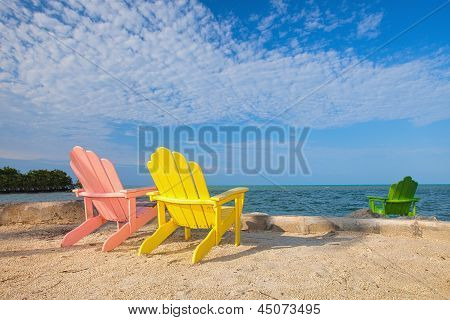 Summer scene with colorful lounge chairs on a tropical beach in Florida