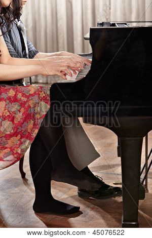 Two people, a couple playing piano duet, showing mostly their hands