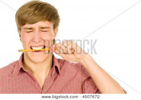 junger Mann beißt einen Bleistift