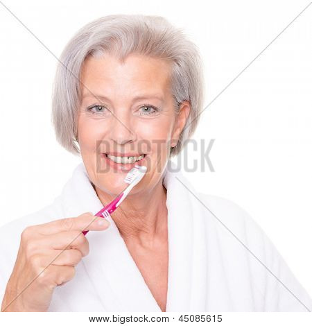 Senior woman with toothbrush in front of white background