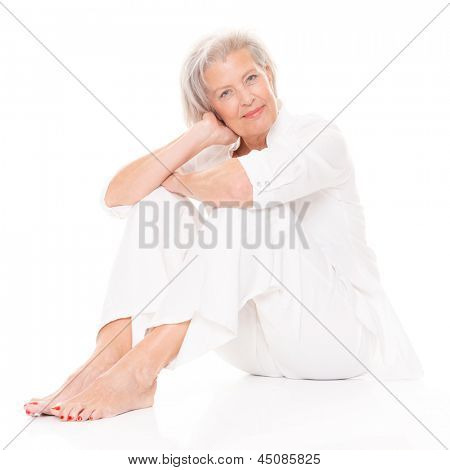 Sitting senior woman in front of white background