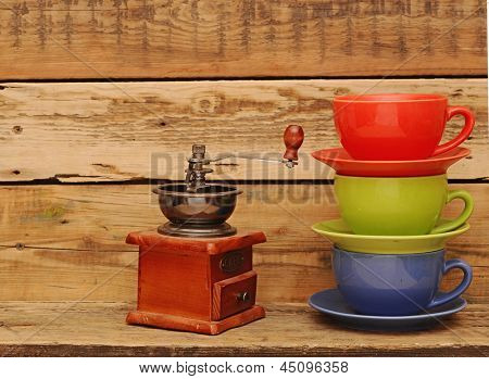 Colorful coffee mugs with coffee mill over an grunge wooden background