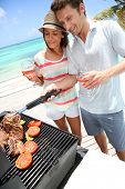 Cheerful couple in holidays preparing grilled meat