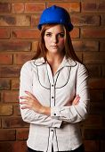 stock photo of blinders  - Beautiful young adult caucasian woman wearing a blue safety hat black pants and a white shirt in front of a brown brick wall with crossed arms - JPG