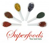 Superfoods in porcelain spoons. Pollen, goji berries, blueberries, spirulina, Hippophae and saffron