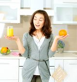 Young and Healthy Funny Woman Choosing between Orange Juice or Whole Orange in the Kitchen. Diet and