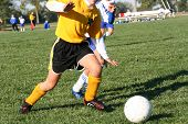 foto of little-league  - young female soccer player dribbling the ball - JPG