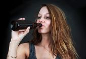 foto of forlorn  - Portrait of drunk young woman drinking beer over black - JPG