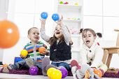 stock photo of daycare  - Young kids playing with each other  in the room - JPG