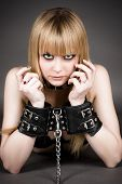 stock photo of debauchery  - beautiful blond in handcuffs isolated on gray - JPG