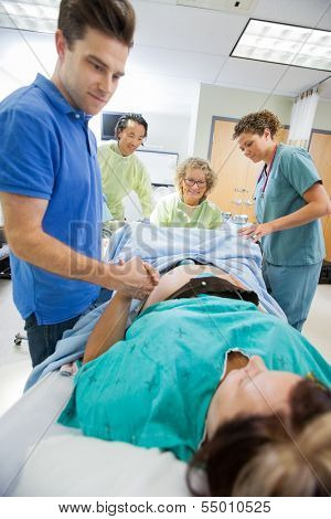 Caring mid adult man holding woman's hand during delivery in hospital room
