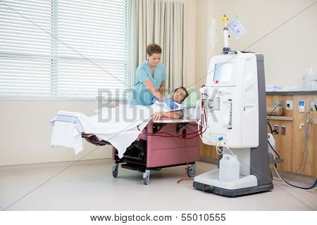 Female nurse covering male patient receiving renal dialysis with blanket in hospital room