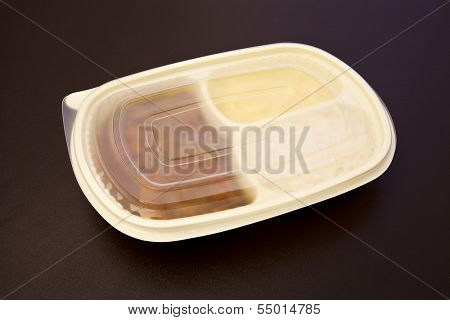 Sole with creole sauce and mashed potatoes in a closed package to go or to freeze. Package on brown leather background.