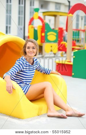 Smiling girl sitting at bottom of yellow slide on the playground