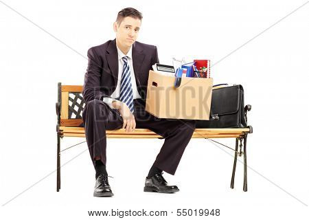 Disappointed redundant businessperson in black suit sitting on a bench with a box of belongings isolated on white background
