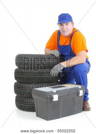 Mechanic wearing blue coveralls and orange t-shirt posing by pile of four new car tires and toolbox shot on white